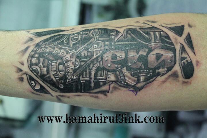 Tatuaje ciborg en el brazo Hamahiru 13 Ink Tattoo & Piercing